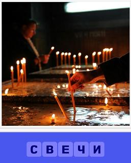 в помещении много горящих свечей и человек зажигает очередную