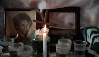Table containing a homemade cross, candles in jars and a photo of a woman