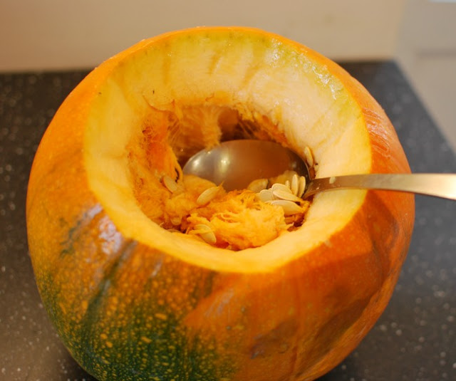 Pumpkin with spoon scooping out seeds