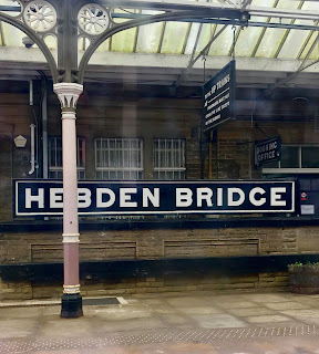A rectangular black plaque with hebden bridge in white font on a large light brown rectangular brick wall on a bright background
