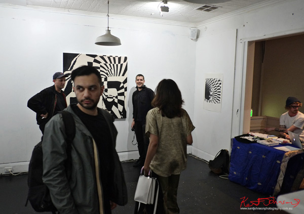 Room shot with art crowd and black and white painting by Joanna Frank. Photographed by Kent Johnson for Street Fashion Sydney.