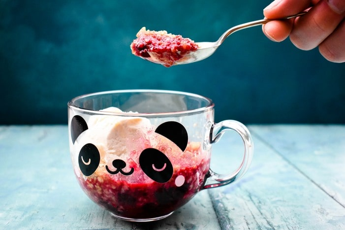 Microwave blackberry crumble in glass mug with panda face