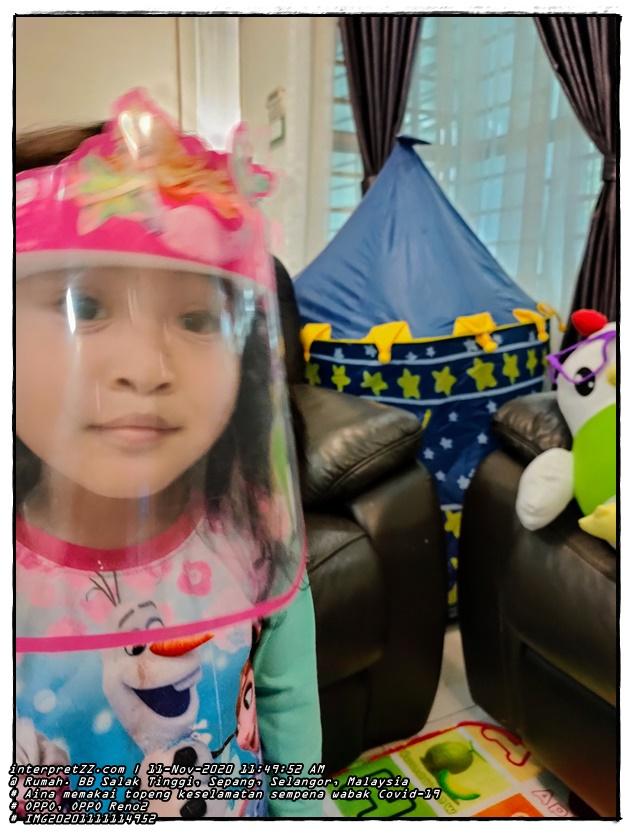 Gambar Aina sedang memakai topeng muka untuk kanak-kanak berwarna merah jambu bertemakan ikan duyung sempena serangan wabak Covid-19 yang melanda seantero dunia. Umur Aina pada masa ini ialah 3 tahun, 8 bulan, dan 21 hari.