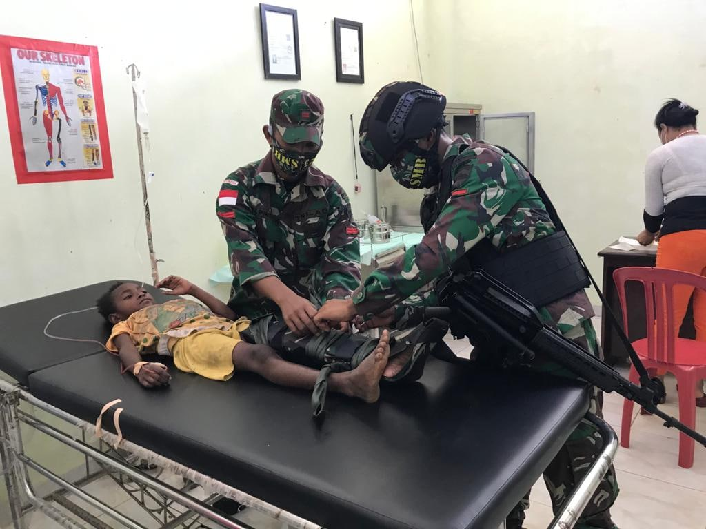 Bitten by a snake, a 7 year old child is helped by TNI soldier
