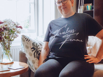Sarah sat on a couch with one hand on her hip wearing a black t shirt that says Fearless Femme