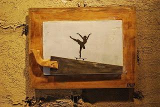 A fotografia mostra um quadro retangular centralizado em uma parede com reboco inacabado pintado em tom mostarda. Na base da tela branca emoldurada com madeira de demolição, está sobreposto um serrote com a parte cortante serrilhada para cima, o cabo de madeira similar à moldura está à esquerda, voltado também acima invadindo parte da moldura. Ao centro da tela, a silhueta em preto de uma bailarina equilibrada com pé esquerdo na ponta, sobre um skate que desliza em declive à direita na parte serrilhada do serrote. A bailarina está com a cabeça elevada, tronco inclinado à frente, braços abertos ao alto com mãos levemente curvas no ar. A perna direita alonga-se para trás na altura da cintura e levanta o tutu armado e curto que ela veste. No canto inferior direito da moldura, a assinatura do artista: Tyler.