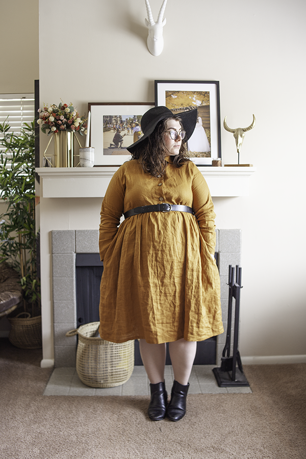 An outfit consisting of an oversized black floppy hat, a golden yellow collared button down linen dress, and black heeled Chelsea boots.