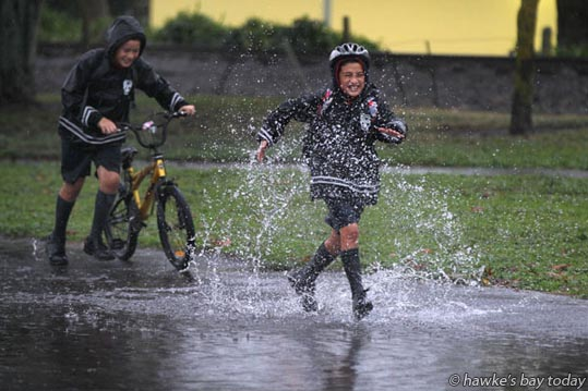 L-R: Chaka Luki, Ezra Aguilar from Hastings Intermediate School, playing in the surface flooding along Karamu Rd South, Hastings. photograph