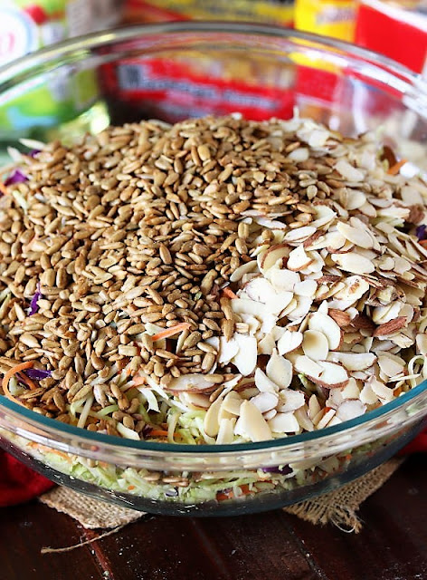 Adding Sunflower Seeds and Sliced Almonds to Bowl of Asian Ramen Noodle Salad with Broccoli Slaw Image