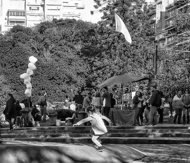 ByN. Nena solita corriendo en la plaza.