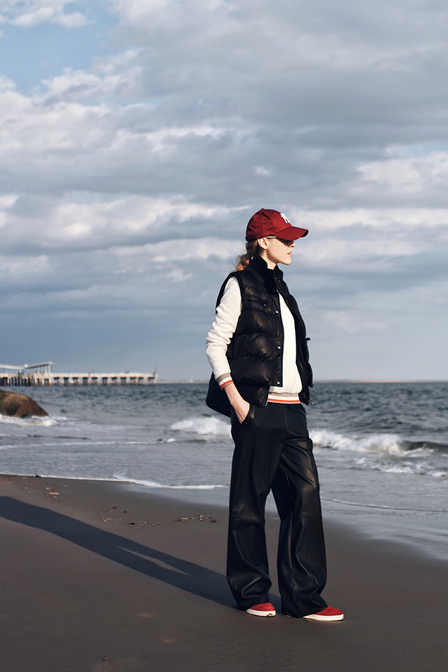 Outfit of the day by Victoria of thewindofinspiration.com, wearing Guess Down Puffer Vest, Hive & Honey Quilted Sweatshirt, Zara Faux Leather Trousers, Ash Cool Wedge Sneakers, New Era New York Yankees Cap.  Pieces Quilted Tote Bag, Marc by Marc Jacobs Aviator Sunglasses, on Coney Island Beach in Brooklyn, NY.