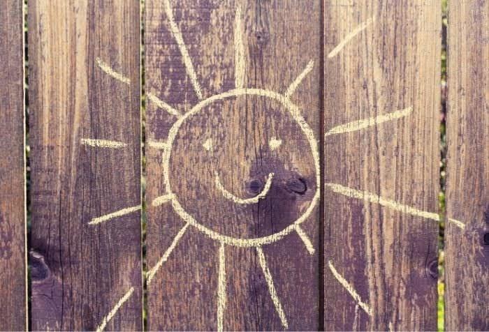 木材に黄色いチョークで描かれたかわいい太陽の絵