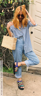 Mulher fazendo um quatro com a perna segurando uma bolsa com fibras naturais e sandália colorida