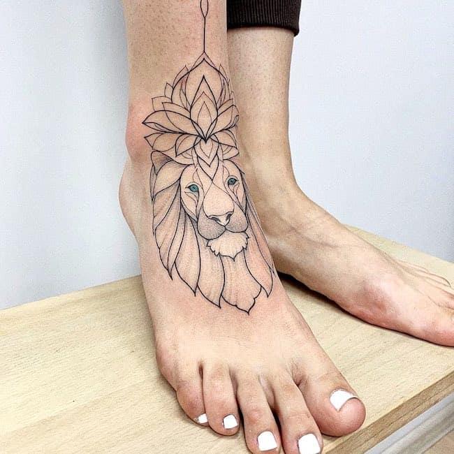 Tatuaje de león elegante para mujer en el pie