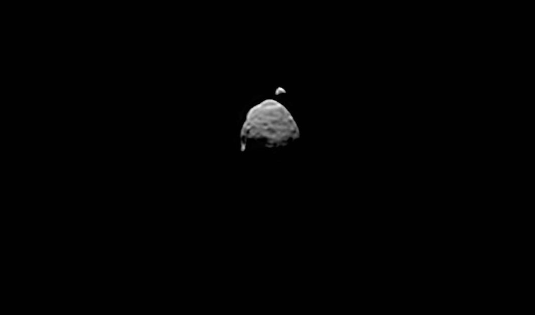 Hai vệ tinh tự nhiên của Sao Hỏa xuất hiện trong cùng một hình ảnh được chụp bởi tàu Curiosity, vật thể lớn hơn là vệ tinh Phobos, đang di chuyển phía trước vật thể có kích thước biểu kiến nhỏ hơn là Deimos, vào ngày 1 tháng 8 năm 2013. Tàu tự hành đã dùng máy ảnh có gắn ống kính phóng to của Mastcam để chụp loạt ảnh về sự che khuất của Deimos bởi Phobos trên bầu trời Sao Hỏa. Bằng việc chụp nhiều hình ảnh, các nhà khoa học mặt đất có thể xử lý và trích xuất ra được nhiều thông tin về những đặc điểm dù là rất nhỏ của hai vệ tinh này. Phần lõm ở cạnh trên của Phobos là Hố va chạm Stickney, đó là khu vực bán cầu bắc của mặt trăng này. Hố va chạm Hall ở bán cầu nam của Phobos, dễ dàng thấy được ở cạnh trái bên dưới. Hình ảnh: JPL-Caltech/Malin Space Science Systems/Texas A&M University/NASA.