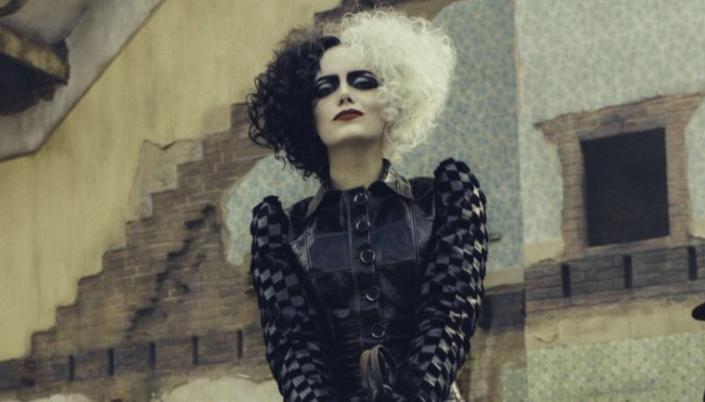 Imagem: a personagem Cruella De Vil interpretada pela atriz Emma Stone, pálida, vestida em couro e roupas pretas com os cabelos pretos e brancos num fundo de um prédio em ruínas.