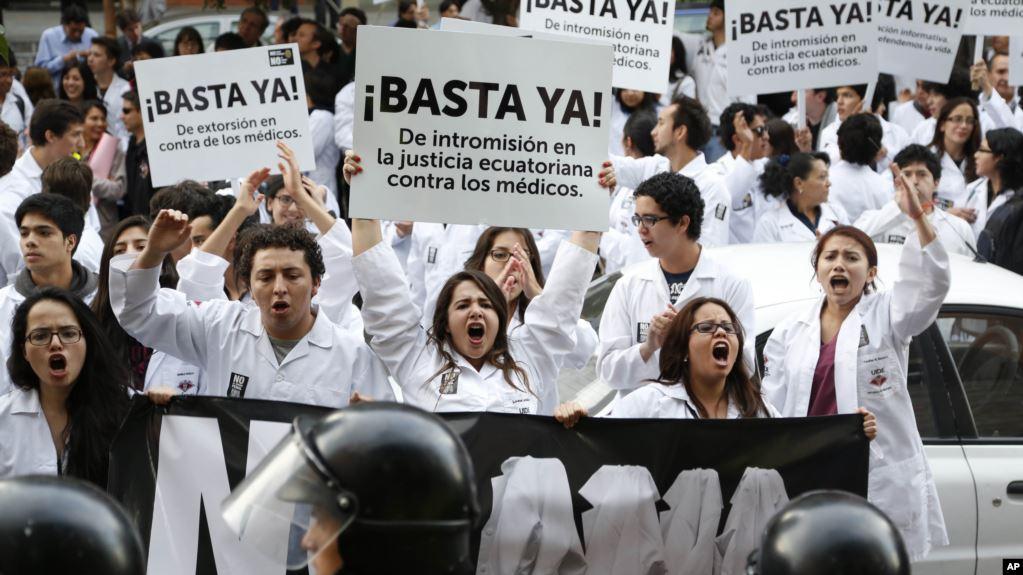 Foto de archivo donde médicos y estudiantes de medicina con pancartas que dicen: