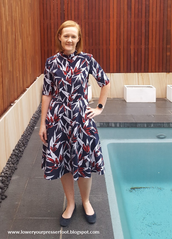 woman posing in a blue and red floral dress next to a swimming pool