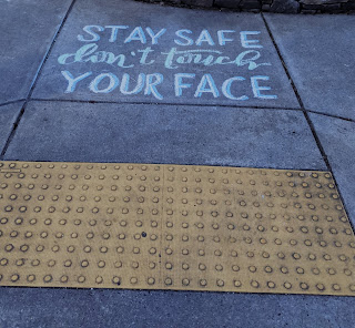 "A sidewalk with chalk that says in bold lettering:  ""Stay safe. Don't touch your face."""