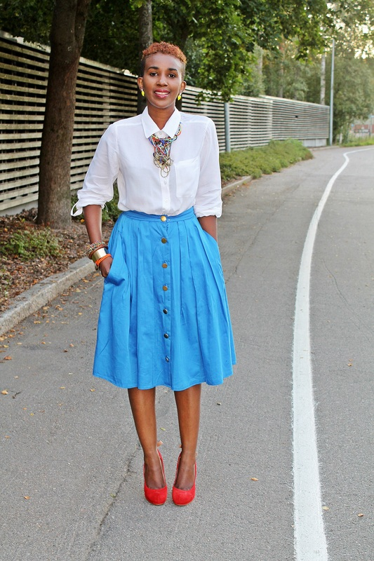 dark skinned lady with short hair is wearing a white shirt, blue skirt, round toe red heels,and accesories