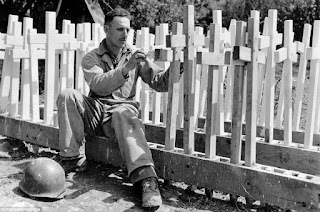 Black & white photo from World War Two showing an American soldier, Alfonton Ortega from LA, making white crosses after the D-day landing.
