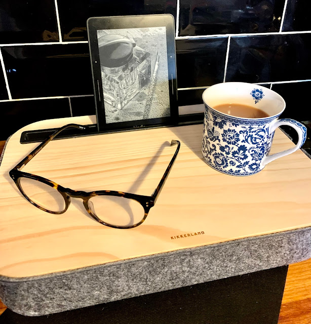 iBED STORAGE lap desk with Kindle in slot, blue and white mug containing tea and glasses on tray.