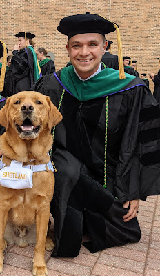 Army Capt. (Dr.) Dmitriy Treyster poses with Shetland the USU live-in facility dog at Treyster's graduation on  May 15th.