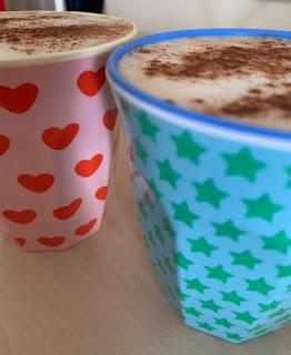 Twee melamine bekers gevuld met havermelk cappuccino