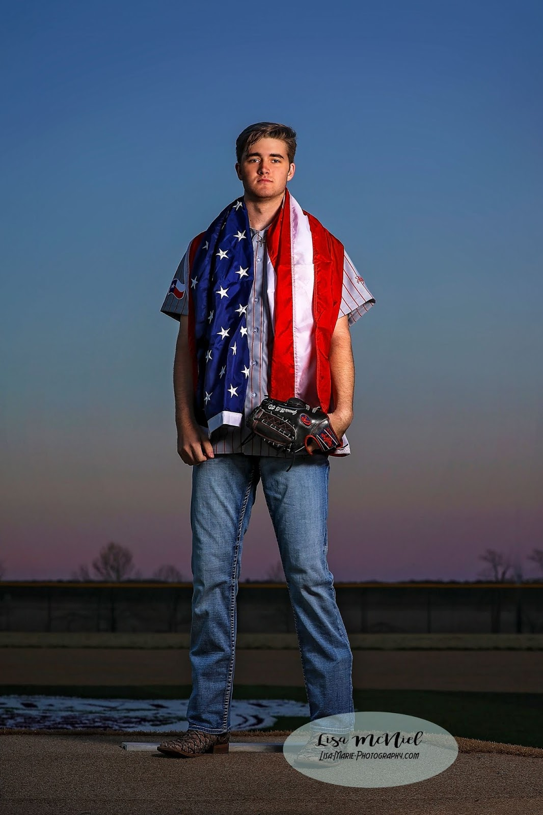 handsome young man in baseball uniform at night with flag around shoulders