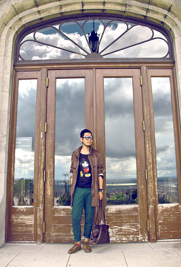 Mickey Mouse T-shirt on Mont-Royal Montreal, man with Zara olive green color raincoat and round sunglasses, brown wool tweed laceless converse sneakers
