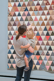a mother and child admire a quilt on the wall of the International Quilt Museum in Lincoln, Nebraska