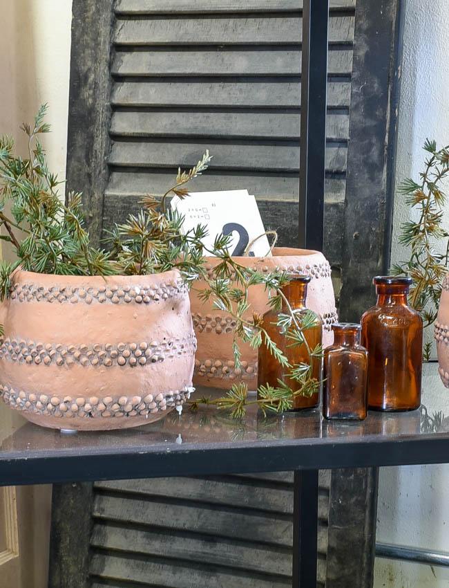 terra cotta vases and amber bottles