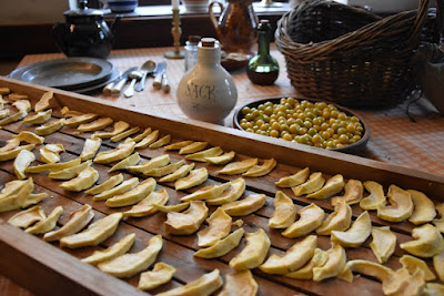 Slices of apple drying on a wooden tray. Pewter plates, a stoneware bottle and other pottery, and a basket are on the table in the background.