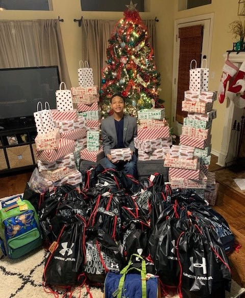 child sitting besides Christmas gifts