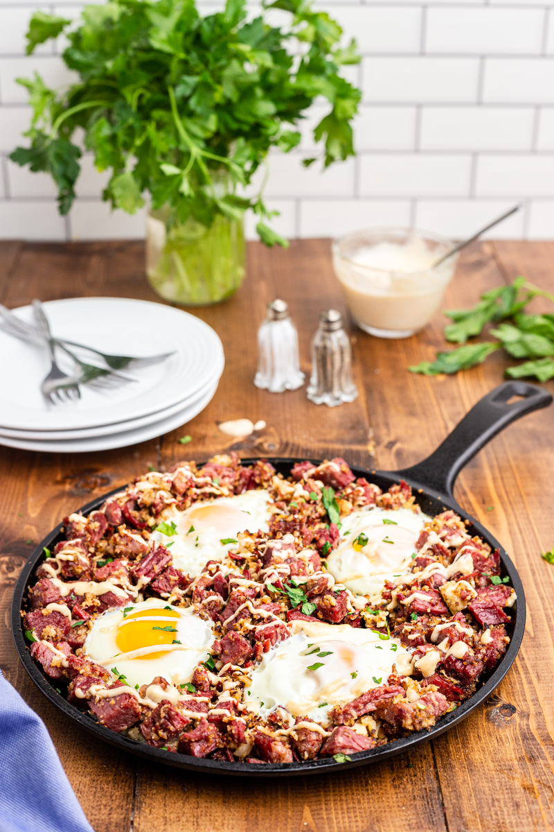 Photo of Keto Corned Beef and Hash in a skillet on a wooden table with a stack of white plates and herbs in the background.