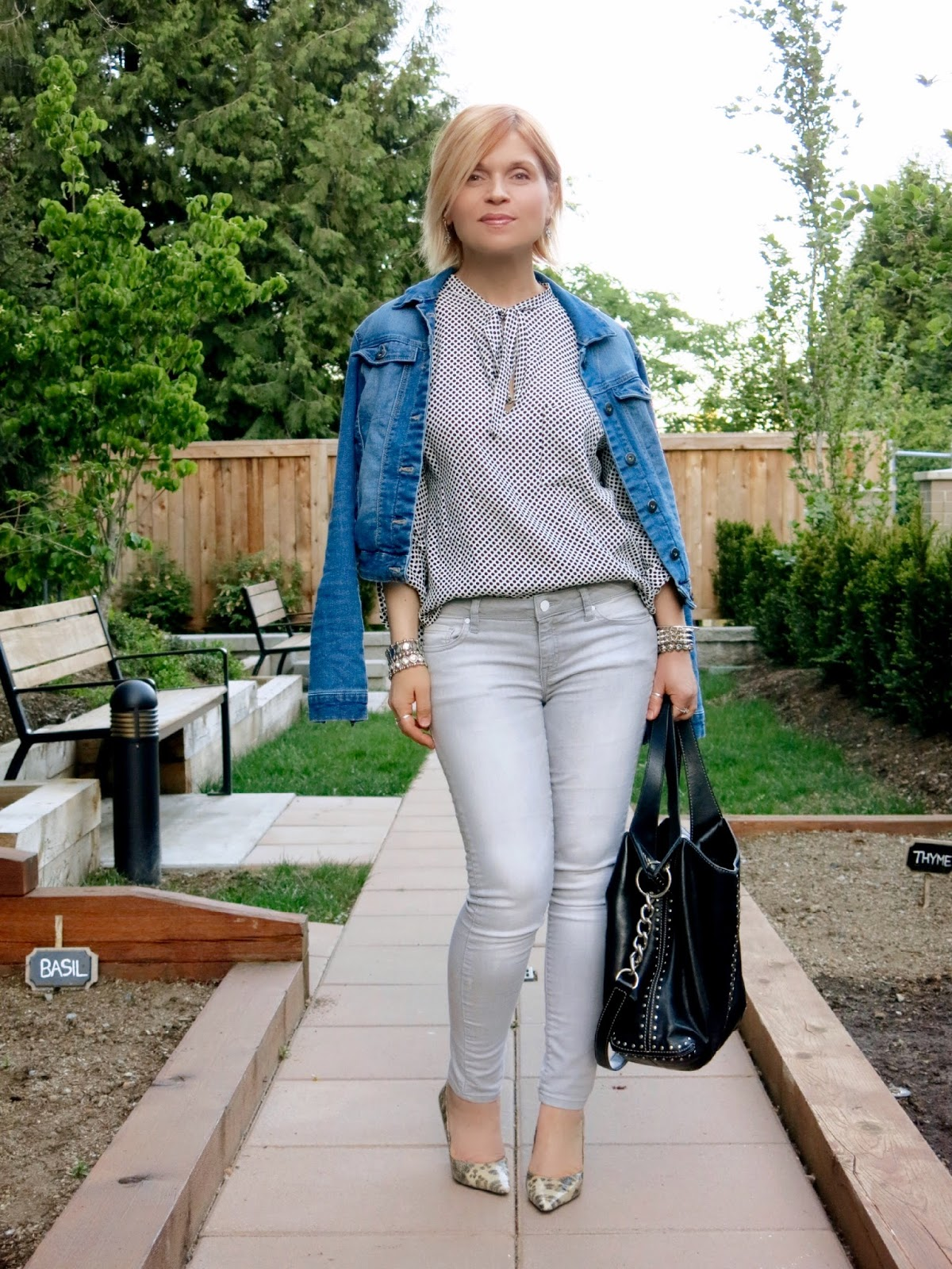 styling grey skinny jeans with a bow-front blouse, denim jacket, and reptile pumps