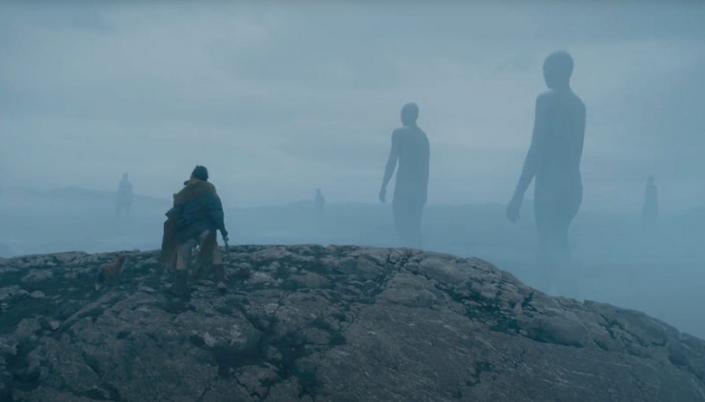 Imagem: a figura de Gawain em cima de um tipo de rocha observando ao longe no meio da névoa várias silhuetas de gigantes, enormes e nus, atravessando o descampado além.