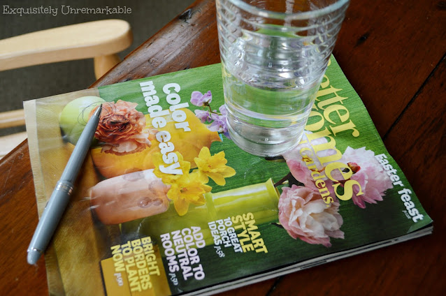 Better Homes and Gardens Magazine on coffee table with pen and cup on top