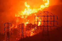 Flames burn near power line (Credit: Mike Eliason/Santa Barbara County Fire Department/AP) Click to Enlarge.
