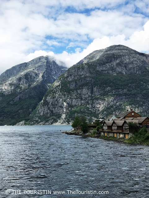 Brown wooden houses at the banks of the Eid Fjord in Eidfjord in Norway.