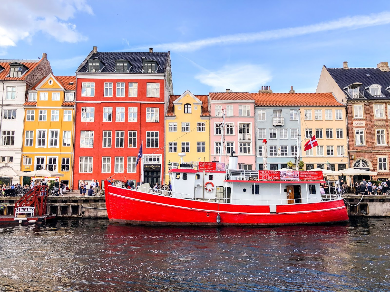 boat on river against colourful houses in typical Copenhagen scene at nyhavn