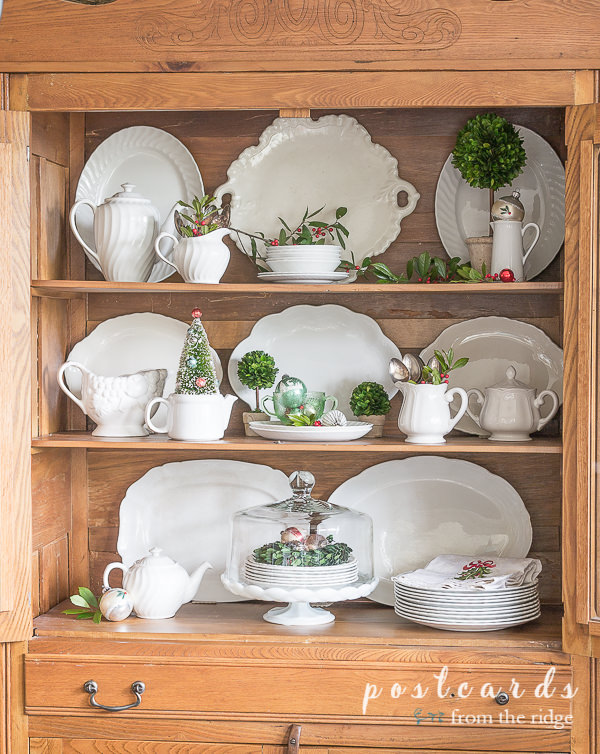 vintage white ironstone platters and pitcher in oak hutch with Christmas decor