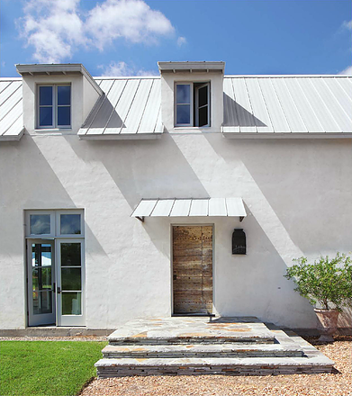 White modern farmhouse stucco exterior and metal roof, Kirby Mears for Eleanor Cummings (found on Hello Lovely)