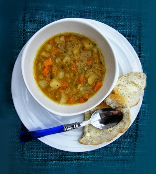 Scottish Tattie, Neep and Carrot Soup in a white bowl served with crusty bread