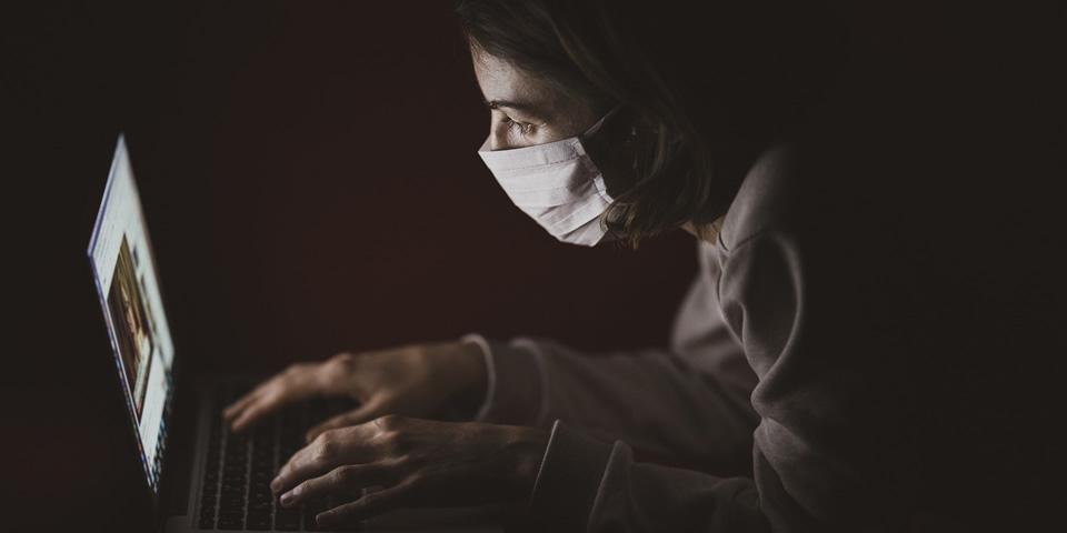 Mulher com máscara facial utilizando um notebook