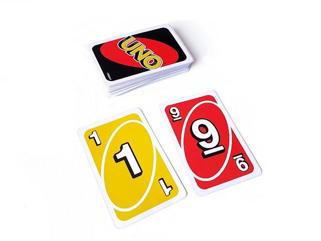 na zdjęciu widzimy zakryty stos kart uno a przed nim leża odkryte żółta jedynka i czerwona dziewiątka