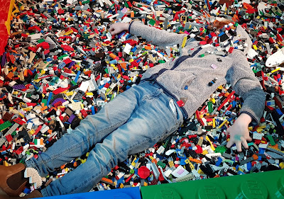 boy lying in LEGO pit with face concealed