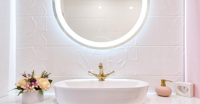 Circular lighted mirror in a white bathroom.