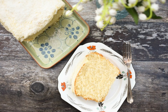 sliced coconut loaf cake topped with buttercream and coconut