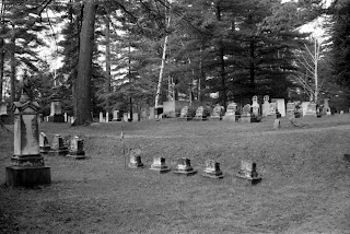 A black and white photograph of a cemetery among trees.